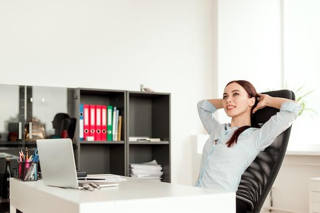 Lächelnde geschäftsfrau, die an dem stuhl an ihrem arbeitsplatz sich entspannt