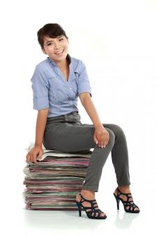 Lächelnde geschäftsfrau, die auf dokumentpapieren sitzt