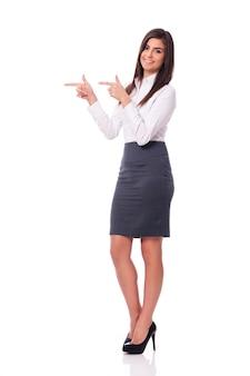Lächelnde geschäftsfrau, die auf kopierraum zeigt