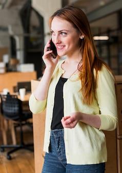 Lächelnde geschäftsfrau, die auf smartphone im büro spricht