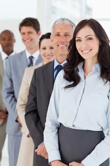 Lächelnde geschäftsfrau, die beim folgen von ihren mitarbeitern überzeugt schaut
