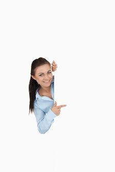 Lächelnde geschäftsfrau, die beim zeigen um die ecke schaut