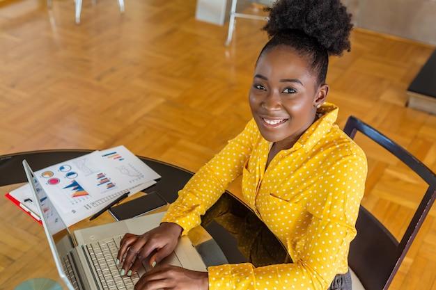 Lächelnde geschäftsfrau, die computer im büro benutzt