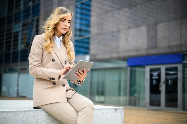 Lächelnde geschäftsfrau, die ein digitales tablett im freien verwendet