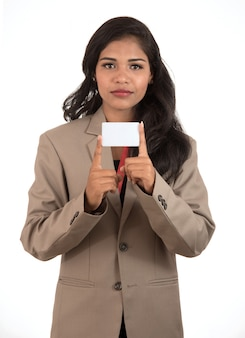 Lächelnde geschäftsfrau, die eine leere visitenkarte oder id-karte über leerraum hält