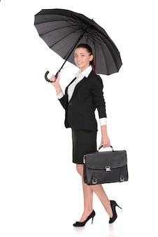 Lächelnde geschäftsfrau, die einen schwarzen portfoliokasten hält.