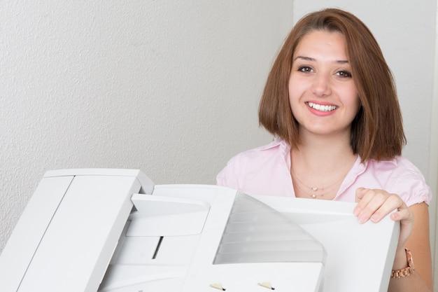 Lächelnde geschäftsfrau, die fotokopiergerät im büro betreibt