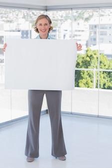 Lächelnde geschäftsfrau, die großes weißes plakat hält