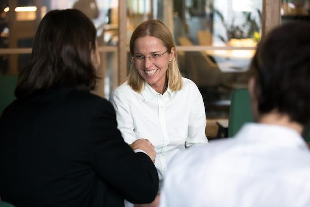 Lächelnde geschäftsfrau, die hand des geschäftsmannes an den verhandlungen oder am interview rüttelt