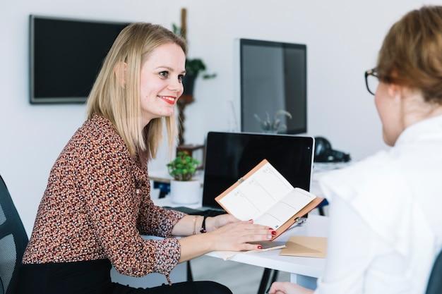 Lächelnde geschäftsfrau, die ihrem kollegen tagebuch zeigt