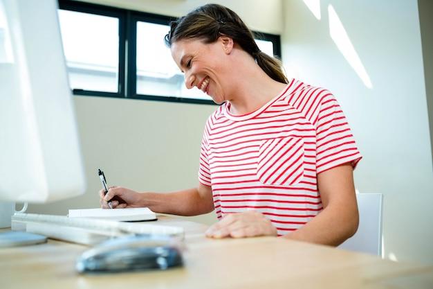 Lächelnde geschäftsfrau, die in ihren notizblock auf ihrem schreibtisch schreibt