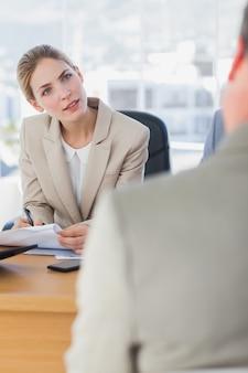 Lächelnde geschäftsfrau, die interviewpartner betrachtet