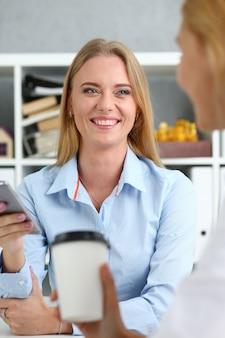 Lächelnde geschäftsfrau, die kaffee von einem pappbecher im büroporträt trinkt, das direkt schaut