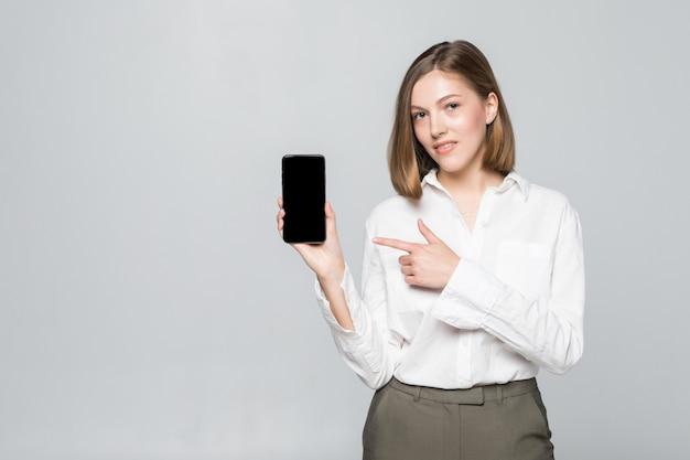 Lächelnde geschäftsfrau, die leeren smartphonebildschirm über grau zeigt