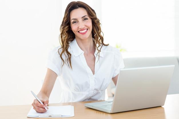 Lächelnde geschäftsfrau, die mit ihrem laptop arbeitet und kenntnisse nimmt