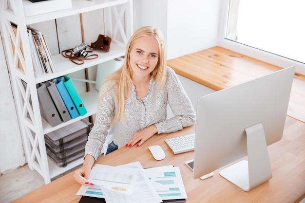 Lächelnde geschäftsfrau, die mit papieren und computer im büro arbeitet