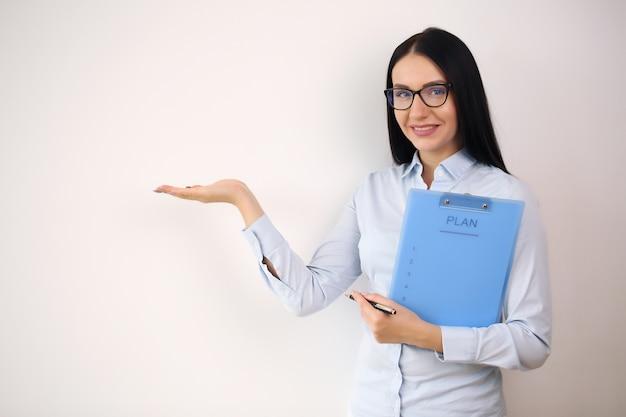 Lächelnde geschäftsfrau, die offene handfläche mit kopienraum für zeigt.