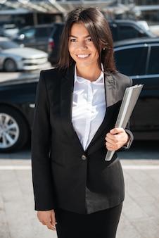 Lächelnde geschäftsfrau, die ordner draußen hält und hält