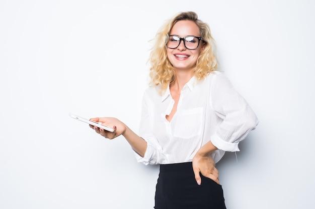 Lächelnde geschäftsfrau, die smartphone über graue wand verwendet. tragen in blauem hemd und brille.