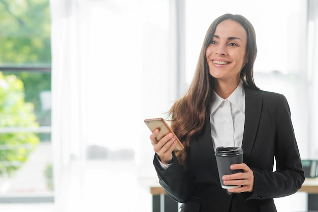 Lächelnde geschäftsfrau, die smartphone und wegwerfkaffeetasse hält