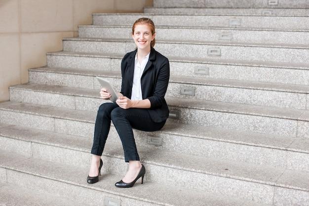 Lächelnde geschäftsfrau, die tablette auf treppe verwendet