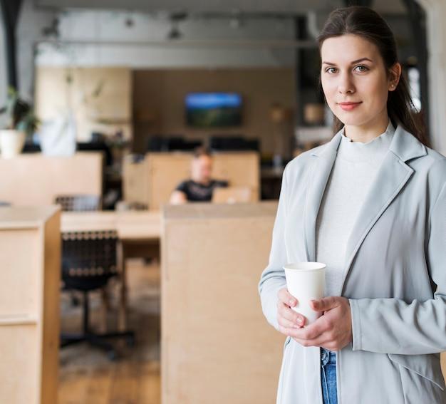 Lächelnde geschäftsfrau, die wegwerfkaffeetasse an arbeitsplatz hält