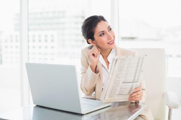 Lächelnde geschäftsfrau, die zeitung beim arbeiten an dem laptop weg schaut hält