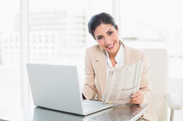 Lächelnde geschäftsfrau, die zeitung beim arbeiten an laptop hält