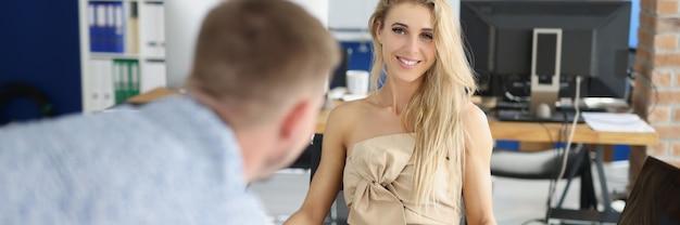 Lächelnde geschäftsfrau hört geschäftsbericht von kollegen