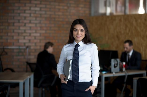 Lächelnde geschäftsfrau in geschäftskleidung, die laptop-computer hält, während zwei männer hinter arbeiten