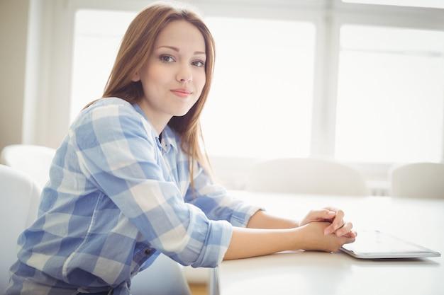 Lächelnde geschäftsfrau mit digitaler tablette im kreativen büro