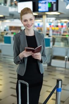 Lächelnde geschäftsfrau mit gepäck, das ihre bordkarte überprüft