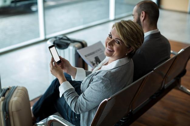 Lächelnde geschäftsfrau mit handy, das im wartebereich sitzt