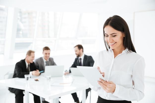 Lächelnde geschäftsfrau mit kollegen am tisch im büro