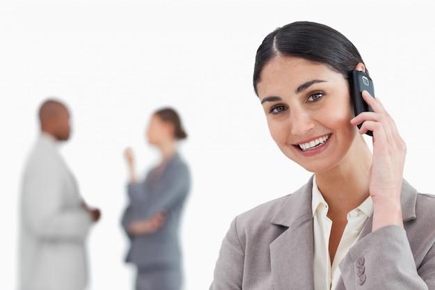 Lächelnde geschäftsfrau mit mobiltelefon und mitarbeitern hinter ihr