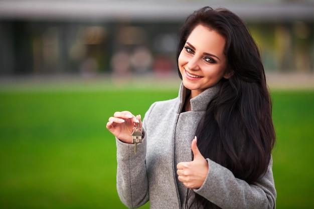 Lächelnde geschäftsfrau mit schlüsseln über büroraum oder neuer wohnung
