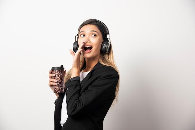Lächelnde geschäftsfrau mit tasse und kopfhörern.