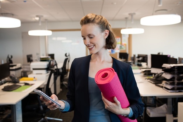 Lächelnde geschäftsfrau mit übungsmatte unter verwendung des mobiltelefons
