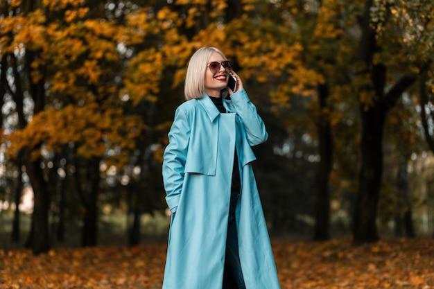 Lächelnde geschäftsfrau mit vintage-sonnenbrille im modischen blauen mantel, die am telefon spricht und im herbstpark mit gelbem laub spazieren geht