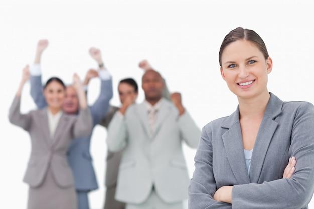 Lächelnde geschäftsfrau mit zujubelndem team hinter ihr