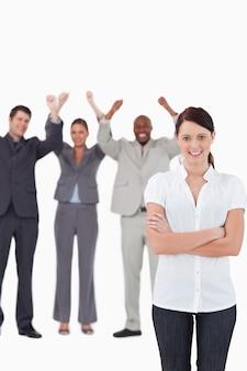 Lächelnde geschäftsfrau mit zujubelnden mitarbeitern hinter ihr