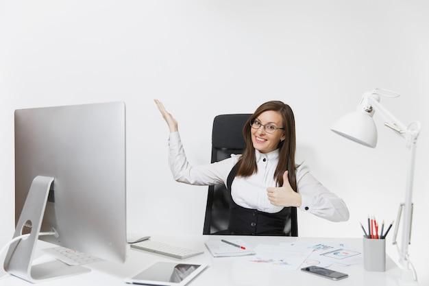 Lächelnde geschäftsfrau sitzt am schreibtisch, arbeitet am computer mit dokumenten im hellen büro und zeigt daumen nach oben,