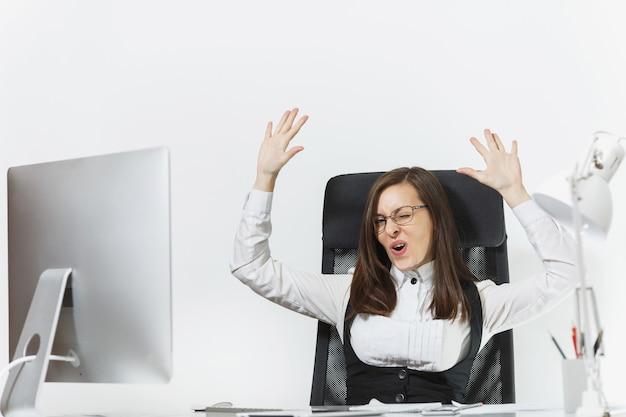 Lächelnde geschäftsfrau sitzt am schreibtisch, arbeitet am computer mit modernem monitor und dokumenten im büro, freut sich über den erfolg, hält die hände hoch, kopiert platz für werbung