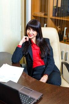 Lächelnde geschäftsfrauen, die am tisch im büro mit schreibarbeit und laptop sitzen