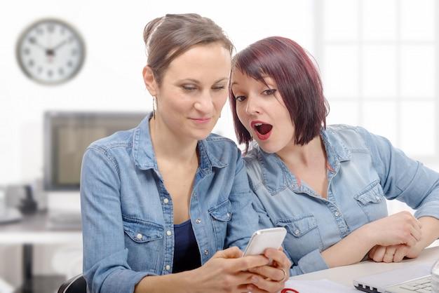 Lächelnde geschäftsfrauen, die handy im büro benutzen