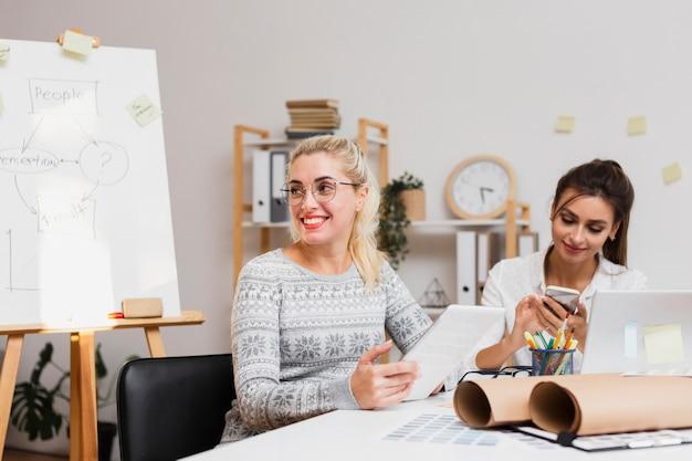 Lächelnde geschäftsfrauen, die im büro sitzen