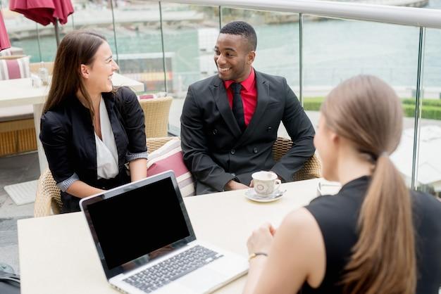 Lächelnde geschäftsleute, die ein treffen im freien haben. erfolgreiche vereinbarungen im gange. brainstorming.
