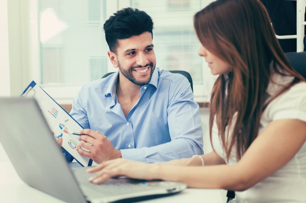 Lächelnde geschäftsleute, die eine laptop-computer in ihrem büro verwenden