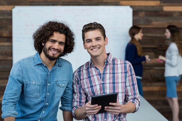 Lächelnde geschäftsleute, die im büro mit digitalem tablett stehen
