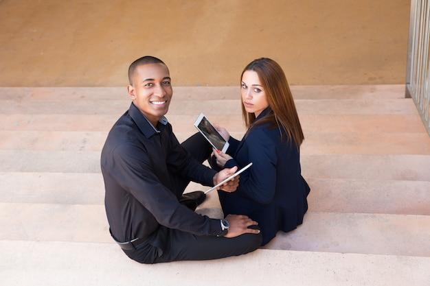 Lächelnde geschäftsleute, die tabletten halten und auf treppe sitzen